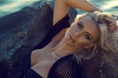 Sluit omhoog portret van schitterende glam gelooide blonde vrouw die het zwarte zwempak en de zomeruniformjas ontspannen op de st stock fotografie