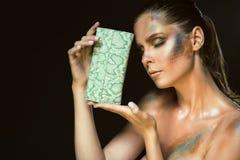 Sluit omhoog portret van schitterende vrouw met gesloten ogen en artistieke snakeskin maakt omhoog het houden van groene leerbeur stock afbeelding