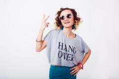 Sluit omhoog portret van schoonheidsvrouw in zonnebril luchtkus, krullend haar, manieruitrusting, jonge hipster Royalty-vrije Stock Foto's