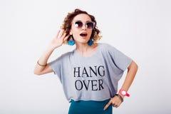 Sluit omhoog portret van schoonheidsvrouw in zonnebril luchtkus, krullend haar, manieruitrusting, jonge hipster Stock Fotografie