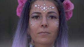 Sluit omhoog portret van sensuele jonge dame met fonkelende make-up doordrongen neus mooie ogen en een bloemkapsel langzaam stock videobeelden