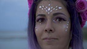 Sluit omhoog portret van sensuele jonge vrouw met fonkelende make-up doordrongen neus mooie ogen en een bloemkapsel langzaam stock footage