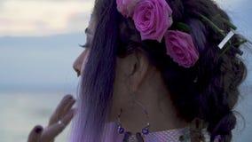 Sluit omhoog portret van sensuele jonge vrouw met heldere make-up doordrongen neus mooie ogen en een bloemkapsel langzaam stock video