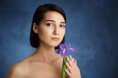 Sluit omhoog portret van teder jong meisje met violette iris over blauwe achtergrond stock foto
