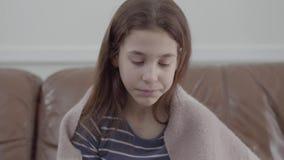 Sluit omhoog portret van tiener die in een deken wordt verpakt die haar neus in een servetzitting thuis blazen op de leerbank stock videobeelden