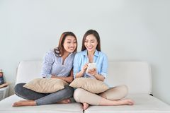Sluit omhoog portret van twee opgewekte meisjes met mobiele telefoons, het lachen stock afbeelding