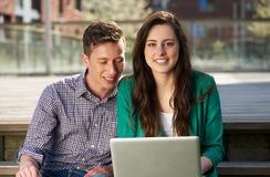 Sluit omhoog portret van twee studenten die aan laptop in openlucht werken Stock Foto's