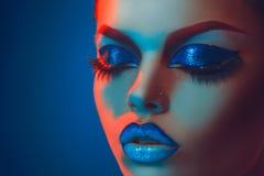 Sluit omhoog portret van volwassen vrouw met gesloten ogen in rood en blu Stock Afbeeldingen