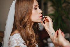 Sluit omhoog portret van vrouw die maquillage doen aan bruid royalty-vrije stock afbeelding