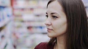 Sluit omhoog portret van vrouw het snuiven douchegel in schoonheidsmiddelenministerie van supermarkt, emotie van gelijkaardig het stock video