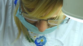 Sluit omhoog portret van vrouwelijke arts in glazen met beschermende het werkslijtage Vrouwelijk gezicht in medisch masker Cosmet stock videobeelden