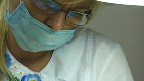 Sluit omhoog portret van vrouwelijke arts in glazen met beschermende het werkslijtage Vrouwelijk gezicht in medisch masker Cosmet stock footage