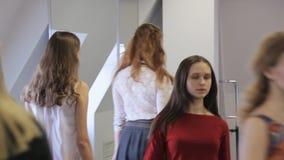 Sluit omhoog portretmening van vrouwen die in modelschool lopen stock videobeelden