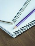 Sluit omhoog potlood en spiraalvormig notitieboekje op houten lijst Royalty-vrije Stock Foto's
