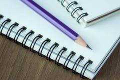 Sluit omhoog potlood en spiraalvormig notitieboekje op houten lijst Stock Foto's