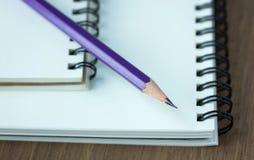 Sluit omhoog potlood en spiraalvormig notitieboekje op houten lijst Royalty-vrije Stock Fotografie