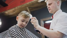 Sluit omhoog Professionele kapper die een nieuw kapsel met behulp van rand en scheerapparaat doen Weinig jongen en stilist of stock footage