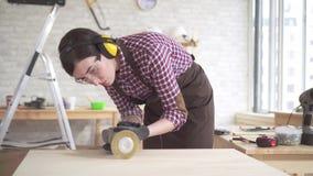 Sluit omhoog professionele timmermansvrouw verantwoordelijk voor het oppoetsen van de houten lijst stock videobeelden