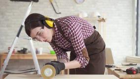 Sluit omhoog professionele timmermansvrouw verantwoordelijk voor het oppoetsen van de houten lijst, langzame mo stock videobeelden