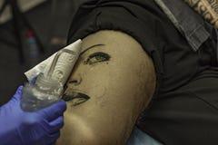 Sluit omhoog professionele vrouwen tattooer schoonmakende tatoegering bij een man le stock foto