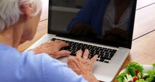 Sluit omhoog rijpe vrouw gebruikend laptop met een salade zettend op de lijst