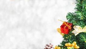 Sluit omhoog rode giftdoos op groene Kerstboom bij witte bokeh lig royalty-vrije stock foto