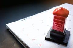 Sluit omhoog rode stuk speelgoed postbus op de maandelijkse ontwerperskalender op zwarte achtergrond Het Programma van de de zome royalty-vrije stock foto