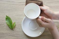 Sluit omhoog schoonmakende de koffiekop van de vrouwenhand op de ochtend met microfiberdoek, stock foto