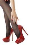 Sluit omhoog Sexy Vrouwenbenen die Glanzend Rood Hoog Hielschoenen en Gray Stockings dragen Stock Afbeeldingen