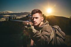 Sluit omhoog sluipschutterskarabijn bij de openlucht jacht Jager die geweer in bosjager met jachtgeweerkanon streven op jacht jag royalty-vrije stock afbeeldingen
