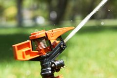 Sluit omhoog sproeiers die water op gras bespuiten royalty-vrije stock foto