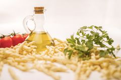 Sluit omhoog stilleven van Italiaanse met de hand gemaakte al van deegwarenfusilli ferretto met tomaten, peterselie en extra eers stock foto