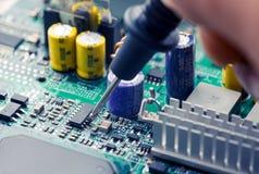 Sluit omhoog - Technicusingenieur die motherboard van de de kringsraad van de multimetercomputer meten stock foto