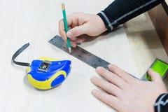 Sluit omhoog Timmerwerk, bemant hand gebruikend meetlint om houten plank te meten en merkend het met potlood Mening van hierboven royalty-vrije stock afbeeldingen
