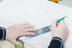 Sluit omhoog Timmerwerk, bemant hand gebruikend meetlint om houten plank te meten en merkend het met potlood Mening van hierboven royalty-vrije stock fotografie