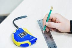 Sluit omhoog Timmerwerk, bemant hand gebruikend meetlint om houten plank te meten en merkend het met potlood Mening van hierboven royalty-vrije stock foto