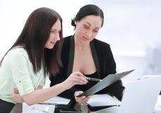 Sluit omhoog twee bedrijfsvrouwen die financiële documenten bespreken stock afbeeldingen