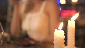 Sluit omhoog twee brandende kaarsen op lijst in avondrestaurant Romantisch diner voor twee met het branden van kaarsen in elegant stock video