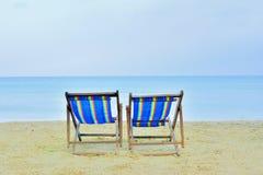 Sluit omhoog twee casvasstoel op strand met zonnige dag overzeese achtergrond Stock Afbeelding