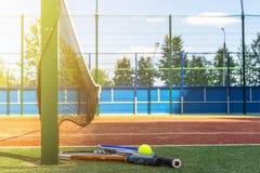 Sluit omhoog twee tennisrackets en een bal ter plaatse dichtbij netto op tennisbaan stock foto