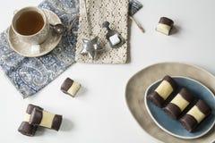 Sluit omhoog Typisch Nederlands cakekoekje met geroepen marsepein en chocolade, mergpijpje Witte lijst, kop thee royalty-vrije stock afbeeldingen