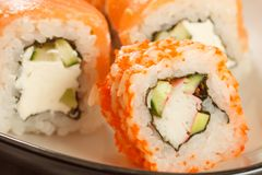 Sluit omhoog Uramaki Californië Sushibroodje met nori, rijst, stukken Stock Fotografie