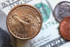 Sluit omhoog van Amerikaanse dollarrekeningen en één dollarmuntstuk stock afbeelding