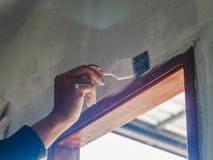 Sluit omhoog van arbeidershand gebruikend rol en borstel voor het schilderen van muur huis in doos op wit wordt geïsoleerd dat stock foto's