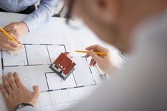 Sluit omhoog van architecten die huisproject bespreken stock afbeelding