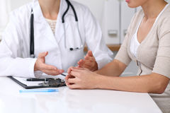 Sluit omhoog van arts en geduldige zitting bij het bureau terwijl arts het richten in medische hystory vorm Geneeskunde a stock foto's