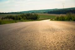 Sluit omhoog van asfalt bij de landweg Asfalttextuur op lege landelijke weg onderaan de heuvel royalty-vrije stock fotografie
