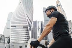 Sluit omhoog van atletische sportman berijdende fiets naast moderne architectuur royalty-vrije stock fotografie