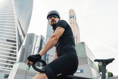 Sluit omhoog van atletische sportman berijdende fiets naast moderne architectuur royalty-vrije stock afbeelding