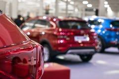 Sluit omhoog van autokoplampen op nieuwe auto's op salon vage achtergrond Het kiezen van uw nieuw voertuig, Autoverkoop, marktpla stock fotografie